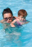 Family in swimming pool playing. Mother and daughter playing in water in swimming pool on sunny summer day, training to swim, healthy lifestyle Royalty Free Stock Photo