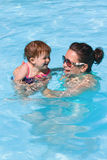 Family in swimming pool playing. Mother and daughter playing in water in swimming pool on sunny summer day, training to swim, healthy lifestyle Royalty Free Stock Photography