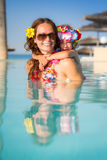 Family in swimming pool. Smiling young women with child playing in swimming pool. Summer vacations concept Stock Photos