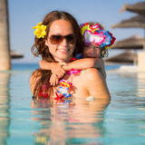 Family in swimming pool. Smiling young women with child playing in swimming pool. Summer vacations concept Stock Image