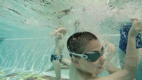 Family at swimming pool. Underwater shot stock footage