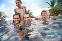 Family swimming in private pool having fun. Family of four enjoying swimming-pool Royalty Free Stock Image