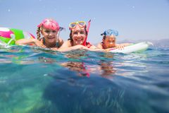 Family swimming in the sea. Happy family with children is swimming and having fun in the sea on an inflatable mattress royalty free stock image