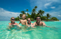 Family swims against the beautiful tropical island Royalty Free Stock Image