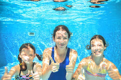 Family swims in pool under water, happy active mother and children have fun, fitness and sport. With kids on summer vacation Stock Photos