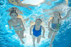 Family swims in pool under water, happy active mother and children have fun, fitness and sport with kids on vacation Stock Photo