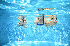 Family swims in pool under water, happy active mother and children have fun, fitness and sport with kids on vacation Stock Images