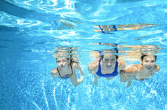 Family swims in pool under water, happy active mother and children have fun, fitness and sport with kids on vacation Royalty Free Stock Image