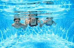 Family swims in pool under water, happy active mother and children have fun underwater, fitness and sport with kids on vacation Royalty Free Stock Photo