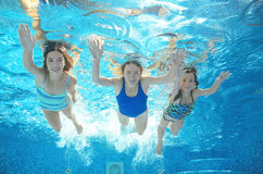 Family swims in pool under water, happy active mother and children have fun underwater, kids sport Royalty Free Stock Photos
