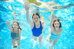 Family swims in pool under water, happy active mother and children have fun underwater, kids sport Royalty Free Stock Image