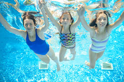 Family swims in pool under water, happy active mother and children have fun underwater, kids sport Royalty Free Stock Photo