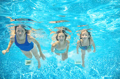 Family swims in pool under water, happy active mother and children have fun underwater, kids sport. On family vacation Royalty Free Stock Images