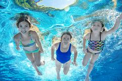 Family swims in pool underwater, happy active mother and children have fun under water, fitness and sport with kids. On summer vacation on resort royalty free stock photo
