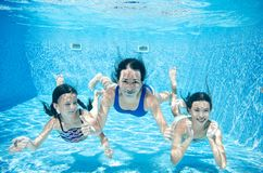 Family swims in pool underwater, happy active mother and children have fun under water, fitness and sport with kids. On summer vacation on resort stock photography