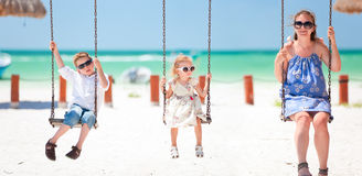 Family swinging. With tropical beach on background stock images