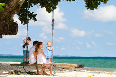 Family swinging on tropical beach stock photos