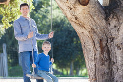 Family at swings. Handsome young father and his little son enjoying time together and having fun in the park swinging Stock Images