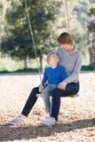 Family at swings Stock Photo