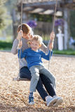 Family at swings Royalty Free Stock Photo