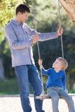 Family at swings Stock Image