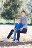 Family at swings Royalty Free Stock Photos