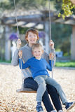 Family at swings Royalty Free Stock Photography