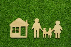 Family symbols and houses made of natural wood on the background of green grass symbolize the eco-house. Conceptual ideas, purchase of sales, credit, mortgage stock image