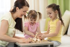 Family at the table playing board game. Family mom and daughters having a fun playing board game at table stock photo