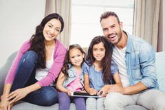 Family with tablet computer sitting on sofa Royalty Free Stock Image