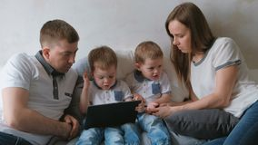 Family with tablet. Mom, dad and two sons twins toddlers looking cartoon at tablet lying on the bed. Family with tablet. Mom, dad and two sons twins toddlers stock video