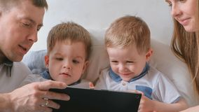Family with tablet. Mom, dad and two sons twins toddlers looking cartoon at tablet lying on the bed. stock photos