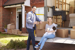 Family On Tail Lift Of Removal Truck Moving Home Stock Photo