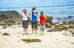 Family takes a photo at the rocky beach Stock Photos