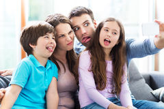 Family taking photo of themselves. Smiling family relaxing at home Stock Photos