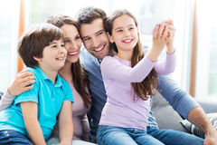 Family taking photo of themselves. Smiling family relaxing at home Royalty Free Stock Photography