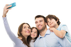 Family taking photo of themselves. Young family with two children on white background stock photography