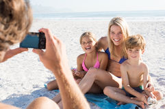 Family taking picture. Father clicking picture of family at beach. Family posing for a photo during summer vacation. Cheerful mother sitting with son and Royalty Free Stock Photo