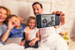 Family taking picture of themselves. Our favorite pastime. Adult smiling father and mother with two their children sitting together in bed and posing for selfie Stock Photography