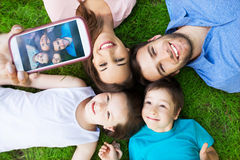 Family taking picture of themselves. Young family lying on grass Stock Photos