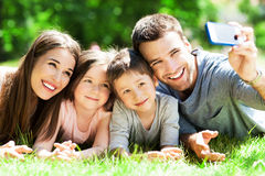 Family taking picture of themselves. Young family lying on grass Royalty Free Stock Photography