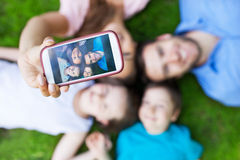 Family taking picture of themselves. Young family lying on grass Stock Photo