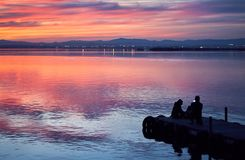 Family taking pictures in the sunset of the calm waters of the Albufera de Valencia, Spain royalty free stock photo