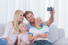Family taking pictures of themselves. In the living room Stock Image