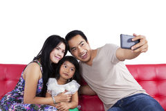 Family taking self picture on sofa Stock Photography