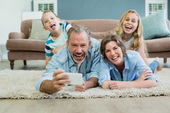Family taking selfie while lying together on the carpet Royalty Free Stock Photography