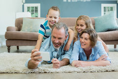 Family taking selfie while lying together on the carpet Stock Photos