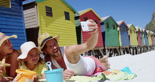 Family taking selfie on mobile phone at beach stock footage