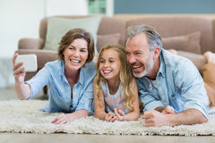 Family taking selfie from mobile phone while lying together on carpet in living room Stock Photography