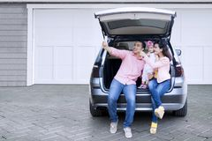 Family taking selfie photo in car. Happy Asian family taking selfie photo together with a smartphone while sitting in the open car baggage stock photo